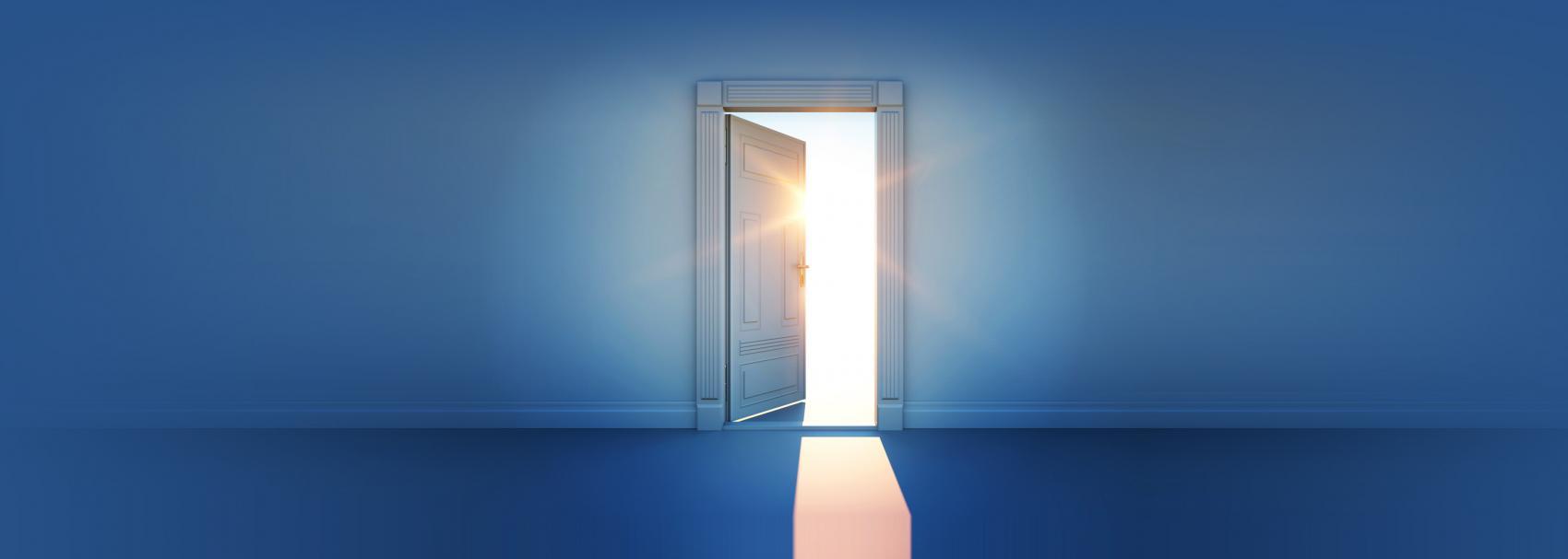 Drzwi na środku w ciemnym pokoju z przebijającym światłem